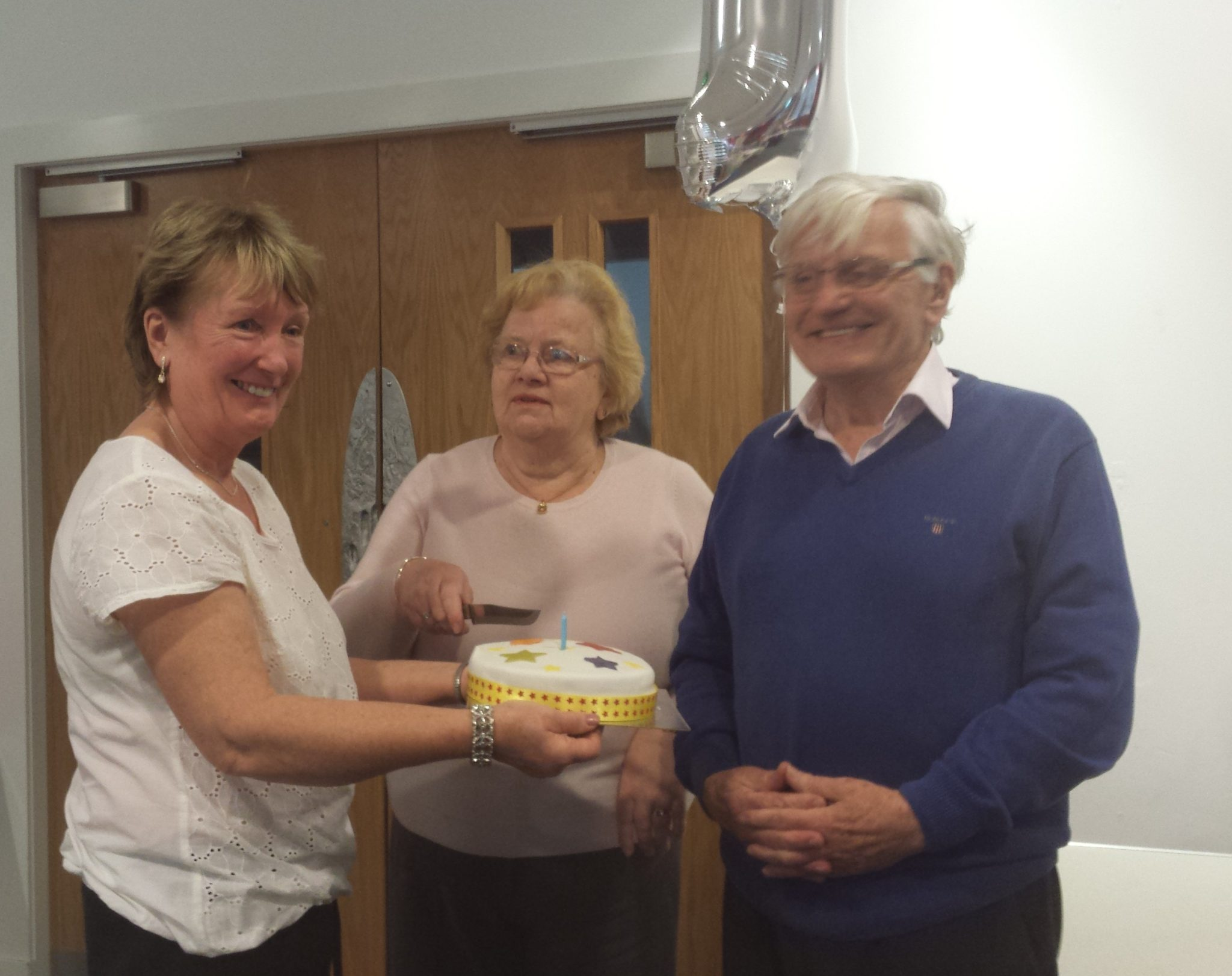Sheila, Ian and Eileen cut the birthday cake