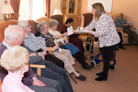 Advocacy Worker standing in front of group of older people in chairs, handing one of them a leaflet.