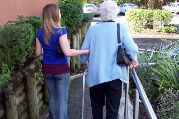White-haired lady being supported by younger lady